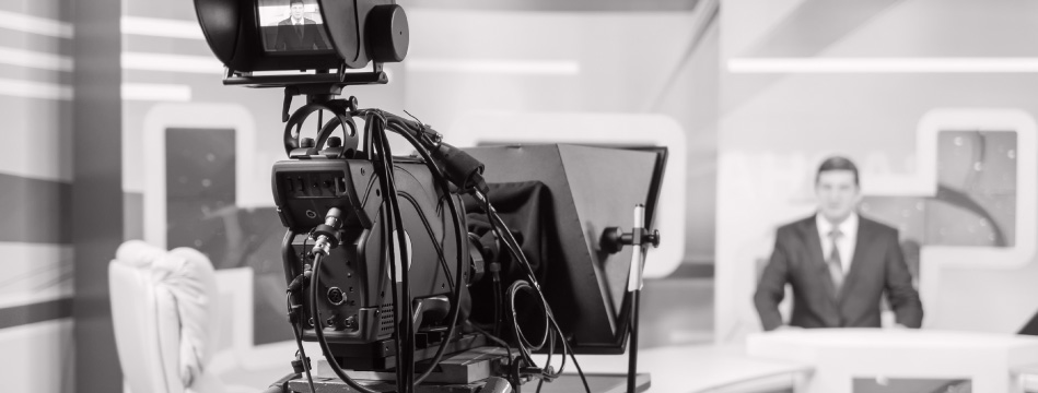 A video camera is filming a news program's anchor